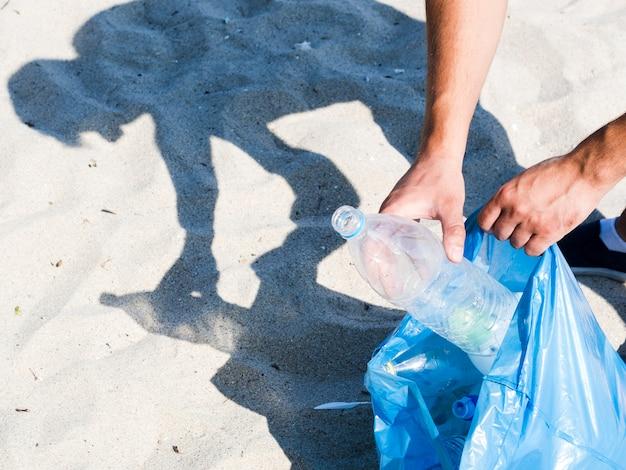 Die hand des mannes, die leere wasserflasche in blauen abfallbeutel auf sand einsetzt