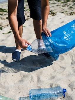 Die hand des mannes, die plastikflasche in blauen abfallbeutel auf strand einsetzt