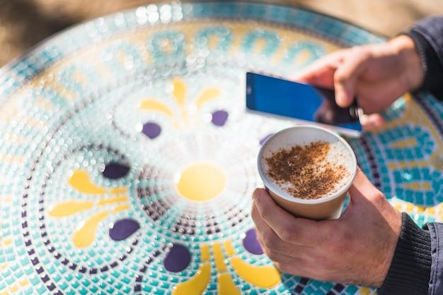 Die hand des mannes, die schalen cappuccino hält, besprühte mit pulverisierter schokolade unter verwendung des handys