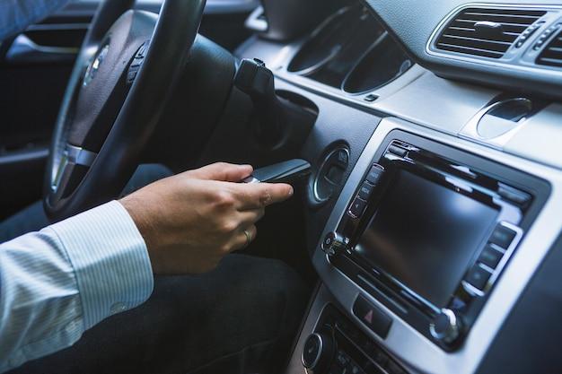 Die hand des mannes, die schlüssel einführt, um auto zu beginnen