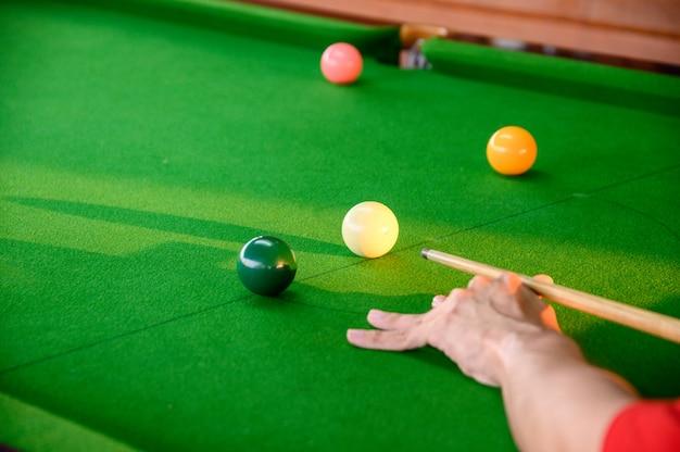 Die hand des mannes, die snooker in der stange mit snookerball spielt