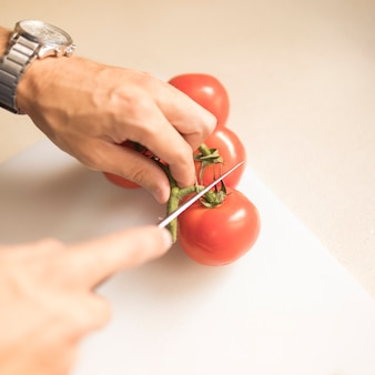 Die Hand des Mannes, die Stamm der roten Tomate mit scharfem Messer auf hackendem Brett schneidet