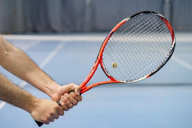 Die hand des mannes, die tennisschläger auf tennisplatz hält