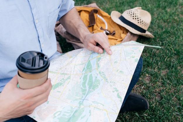 Die hand des mannes, die wegwerfkaffeetasse hält und bestimmungsort auf karte beim sitzen im park sucht