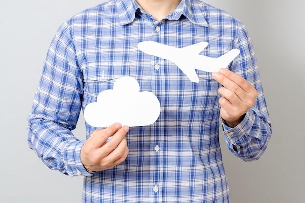 Die hand des mannes, die weißbuchmodell des flugzeuges und der wolke hält