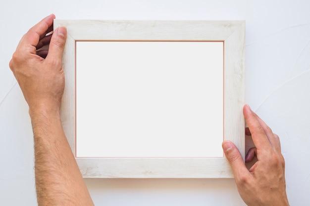 Die hand des mannes, die weißen bilderrahmen auf wand setzt