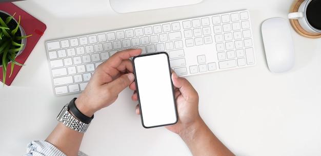 Die hand des mannes, die weißen schirmhandy auf schreibtisch im büro hält