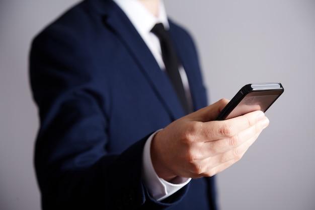Die hand des mannes, die weißes hemd und anzugwand, nahaufnahme, geschäftskonzept trägt, hält ein mobiltelefon, mit telefon-app.