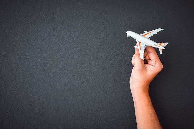 Die hand des mannes, die weißes spielzeugflugzeugmodell über schwarzem farbwandhintergrund hält