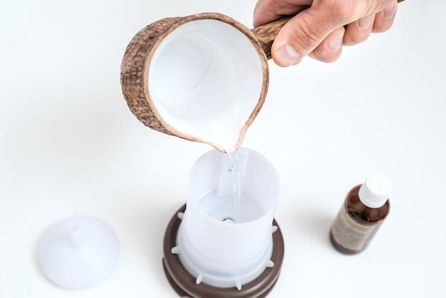 Die hand des mannes füllt mit wasser eine kapazität des aromadiffusors.