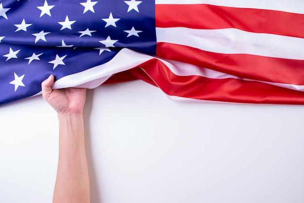 Die hand des mannes hält amerikanische flaggen gegen einen weißen hintergrund.