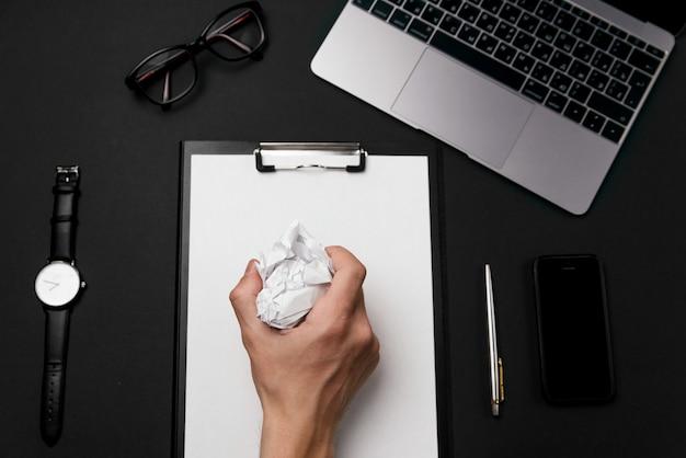 Die hand des mannes hält das zerknitterte papier. schwarzer schreibtisch mit laptop, telefon und zubehör.
