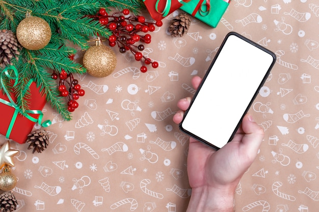 Die hand des mannes hält ein handy auf weihnachtsdekorationshintergrund. weihnachts- und neujahrsdekorationen und geschenke im hintergrund.