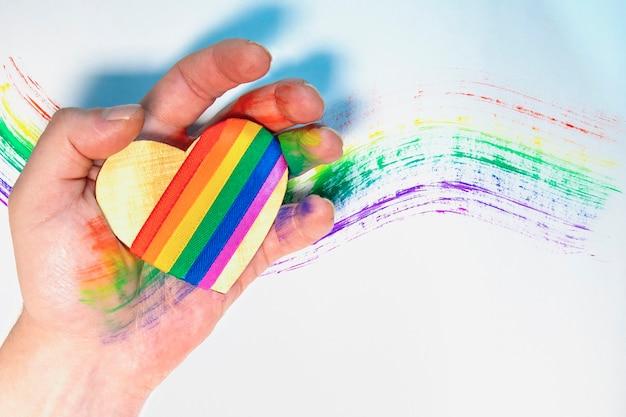 Die hand des mannes hält ein herz mit lgbt symbolen. gezeichneter regenbogen im hintergrund. freie liebe. lesbian gay bisexual transgender. valentinstag. Premium Fotos