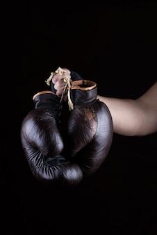Die hand des mannes hält ein paar alte lederne braune boxhandschuhe