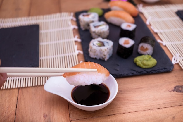Die hand des mannes hält ein paar stäbchen und ein nigiri-sushi über der sojasauce. holztisch