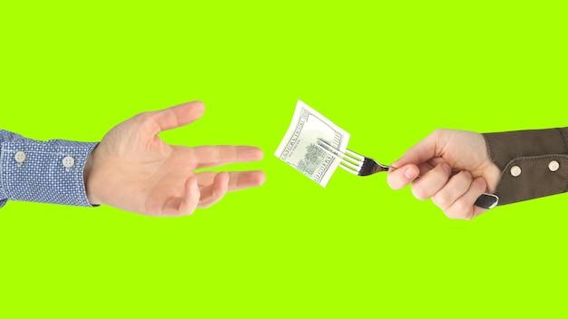 Die hand des mannes hält eine gabel mit einem dollarschein in der anderen hand auf kalk