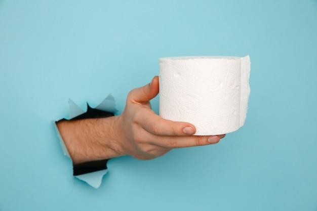 Die hand des mannes hält eine rolle toilettenpapier an einer blauen wand