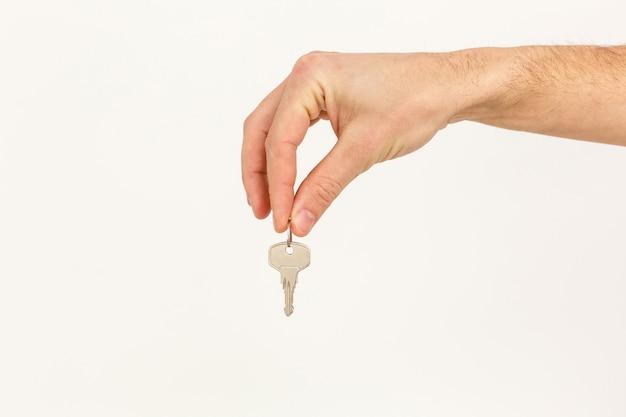 Die hand des mannes hält einen schlüssel, der auf einem weißen hintergrund lokalisiert wird