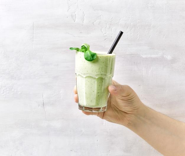 Die hand des mannes hält grünes gesundes smoothie-glas mit strohhalm