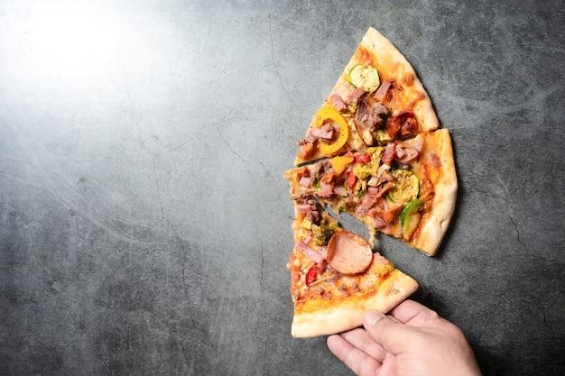 Die hand des mannes hält stück pizza