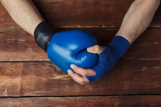 Die hand des mannes in den boxverbänden hält eine hand in einem boxhandschuh auf einem hölzernen hintergrund. bereit geste. konzept des trainings für boxtraining oder kampf.