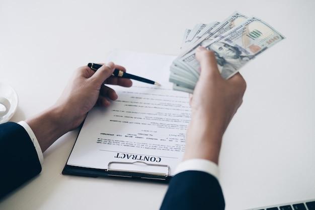 Die hand des mannes in der klage, die bargeld gibt und stiftpunkt zum unterzeichnen verwendet
