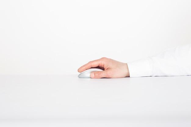 Die hand des mannes ist auf der modernen drahtlosen berührungsmaus auf einem weißen hintergrund. cybersicherheitskonzept.