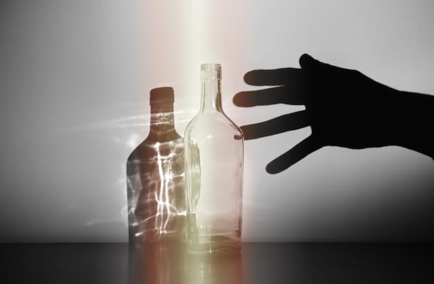 Die hand des mannes mit alkoholflaschensilhouette. alkoholsüchtiger. gefährliche gewohnheit. ungesundes lebenskonzept. soziales problem.