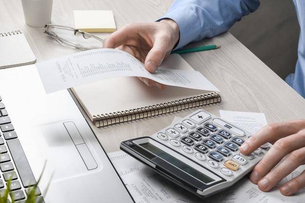 Die hand des mannes mit taschenrechner und schreiben notieren sie sich mit der berechnung von kosten und steuern im homeoffice. geschäftsmann, der am arbeitsplatz papierkram erledigt