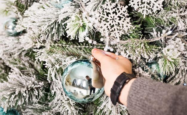 Die hand des mannes mit weihnachtskugeln. winter-, party-, neujahrs- und weihnachtskonzept