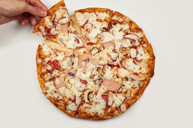 Die hand des mannes nimmt ein köstliches stück pizza mit margarita oder margarita mit mozzarella-käse