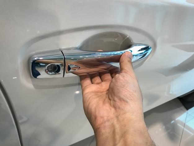 Die hand des mannes öffnet den autotürhintergrund