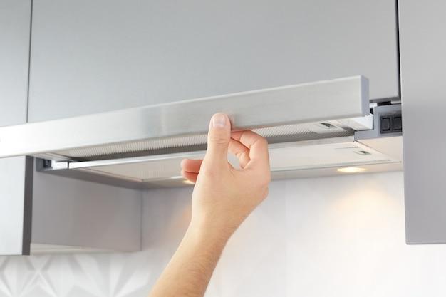 Die hand des mannes öffnet die dunstabzugshaube zum kochen oder ersetzen des filters. modernes interieur auf hintergrund.