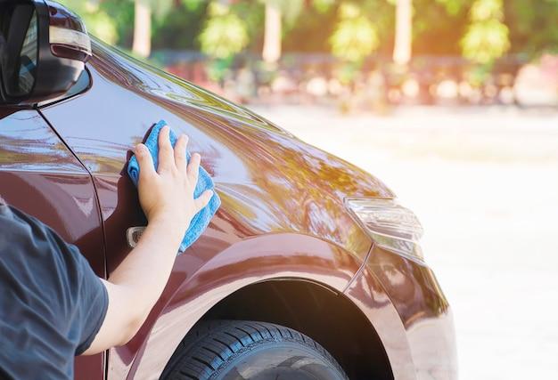 Die hand des mannes reinigt und wächst das auto