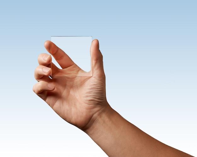 Die hand des mannes repräsentiert ein transparentes glas auf einem blauen hintergrundplatz für text