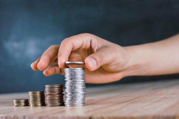 Die hand des mannes setzte geldmünzen zum stapel münzen.