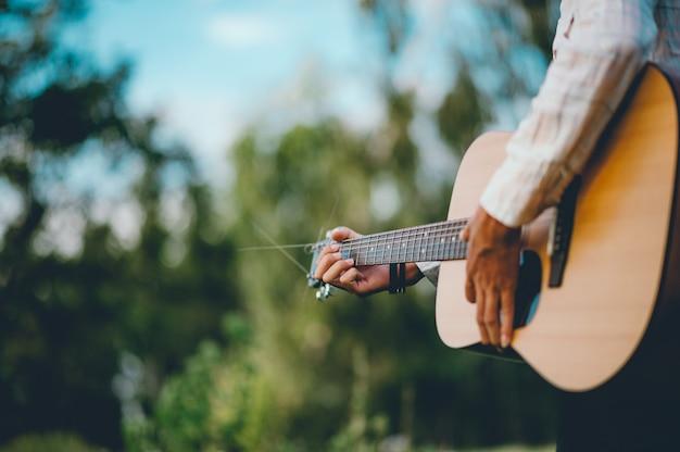 Die hand des mannes spielt die akustische gitarre, spielt gitarre allein im garten