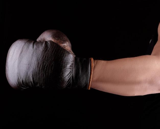 Die hand des mannes trägt einen braunen lederboxhandschuh