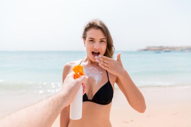 Die hand des mannes trägt im sommerurlaub am strand plötzlich sonnencreme auf die brust einer überraschten frau auf.