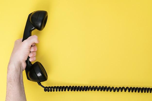 Die hand des mannes, welche die wechselsprechanlage eines alten telefons hält