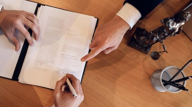 Die hand des mannes zeigt mit dem finger, wo er die unterschrift setzen soll.