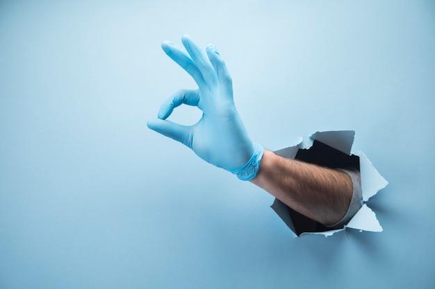 Die hand des mannes zeigt sich in handschuhen auf einer blauen szene in ordnung