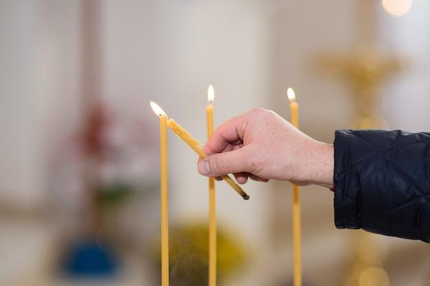 Die hand des mannes zündet eine kerze in einer kirche an