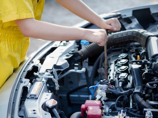 Die hand des mechanikers misst den motorölstand