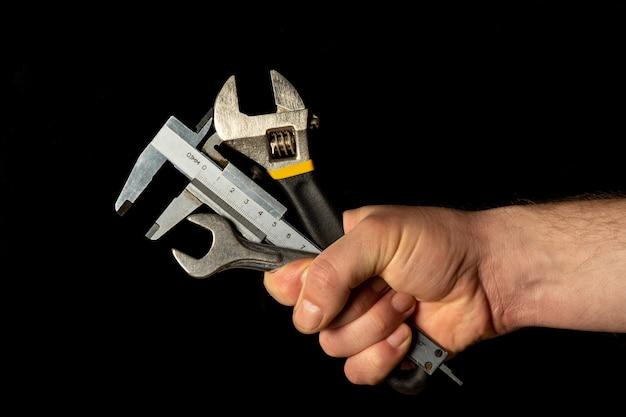 Die hand des meisters hält eine reihe von werkzeugen zur reparatur von rohrleitungen