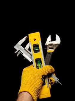 Die hand des meisters hält eine reihe von werkzeugen