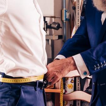 Die hand des modedesigners, die maß der taille seines kunden mit gelbem messendem band nimmt