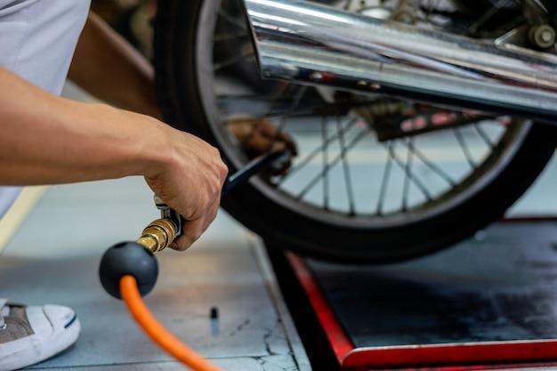 Die hand des nahaufnahmemannes, die reifenluft mit einem manometer im autoreparaturservice überprüft