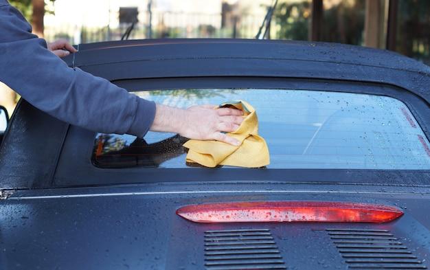 Die hand des nahaufnahmemannes wäscht ein auto. hand hält schwamm, um auto zu waschen